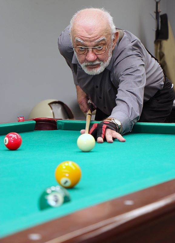 Elderly Man Prepares to Hit the Cue Ball in a Game of Pool